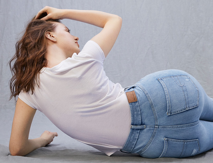 Woman wearing light wash AE Curvy Jeans and a white t-shirt