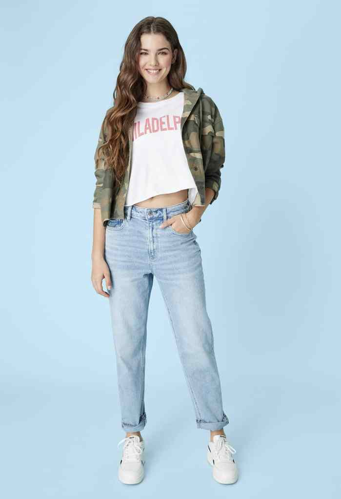 woman wearing a camo hoodie, white t-shirt, and light wash Mom straight jeans