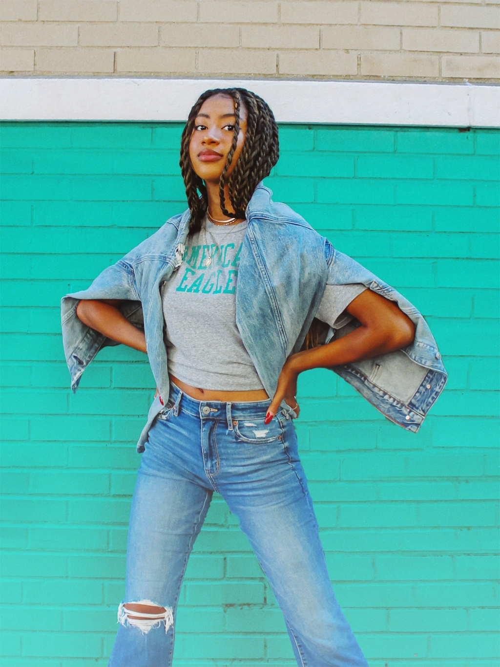 woman wearing a graphic tee, jean jacket and ripped jeans