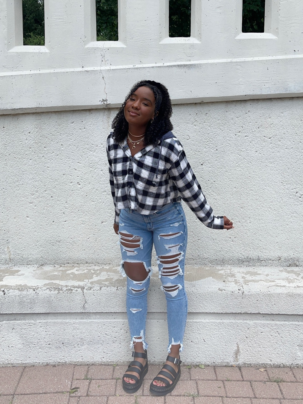 woman wearing a black and white flannel and light wash ripped jeans