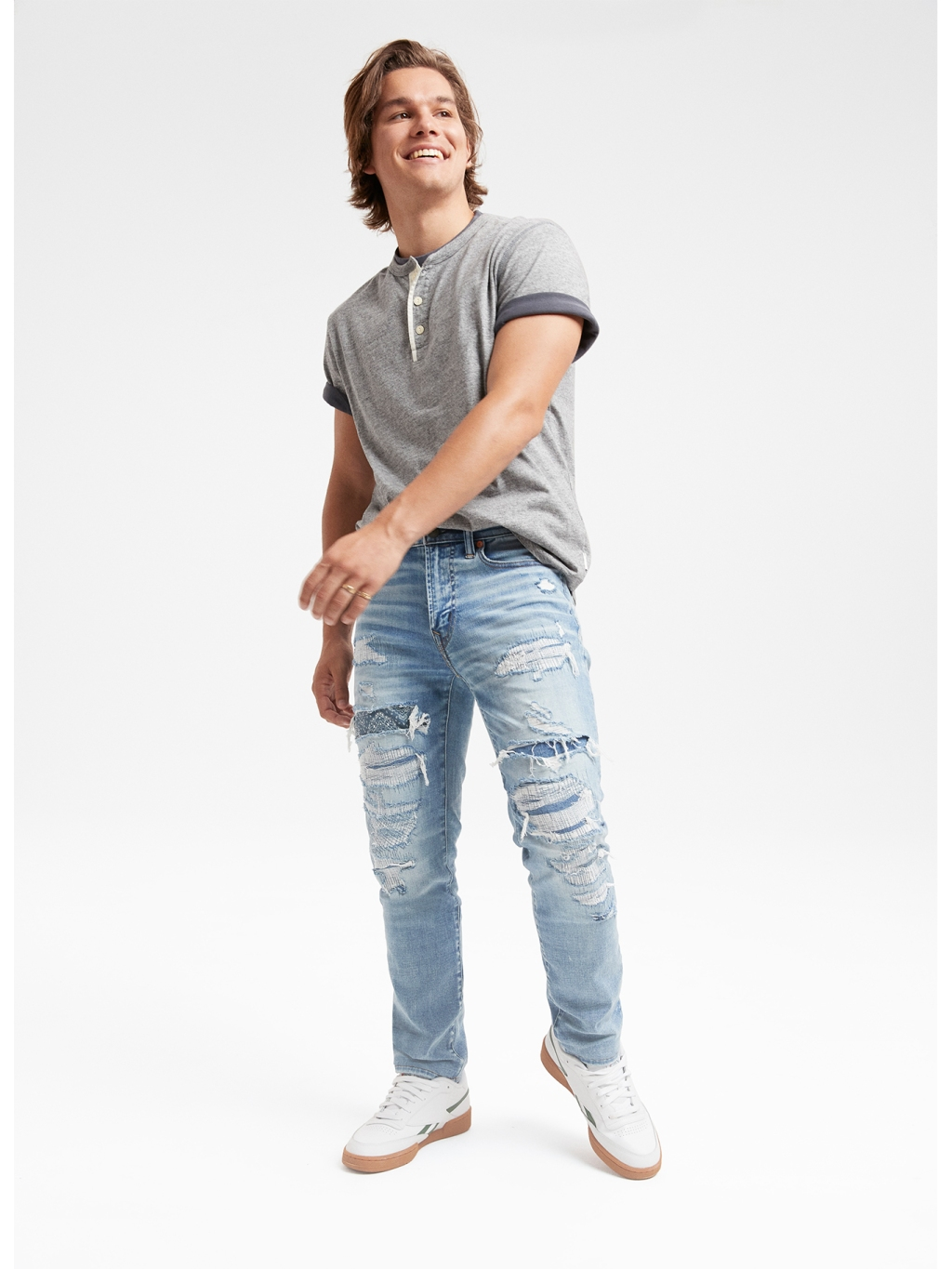 guy wearing a gray tshirt and light wash slim jeans